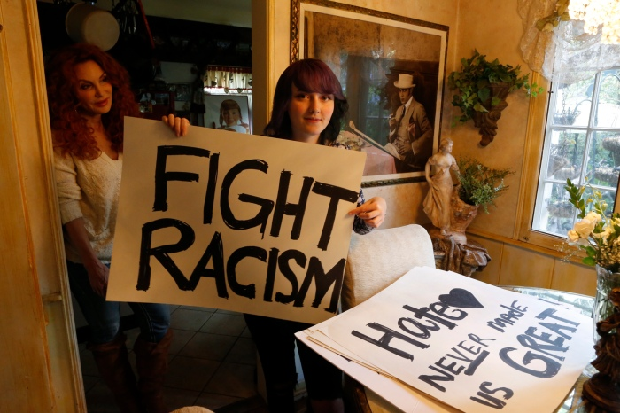 In this Monday, Nov. 21, 2016, photo, high school student Amellia Sones, 14, who helped organize a Ventura Boulevard protest after the presidential election, poses with her signs inside her home in Los Angeles. At left, her mother, Emmy nominated celebrity makeup artist, DeeDee Marcelli looks on. Around the country, even as protests have waned, Democrats say the sting of loss has left an impact unlike any past presidential race, stirring previously passive citizens to push beyond their initial tears and angry Facebook posts following Donald Trump's win. (AP Photo/Damian Dovarganes)