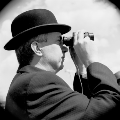 Man in bowler hat looking through binoculars
